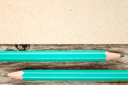 copyspace: Wooden background with two pencils and cardboard for copy-space
