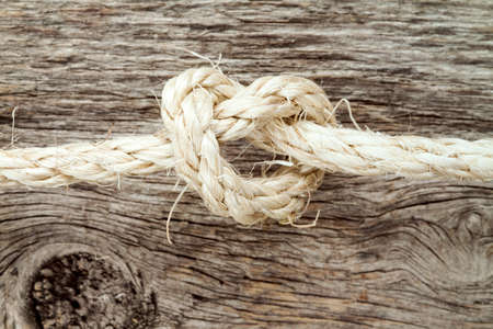 sisal: Sisal rope with knot on the wooden background