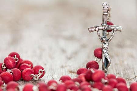catholic symbol: Catholic rosary on old wooden  background. Selective focus.