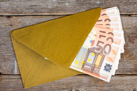 batch of euro: Golden envelope with Euro bills over wooden background Stock Photo