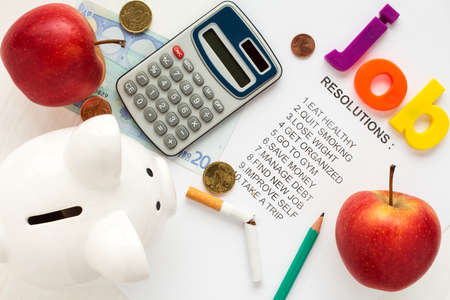 office supply: Piggy-bank,apples and office supply on list of resolutions