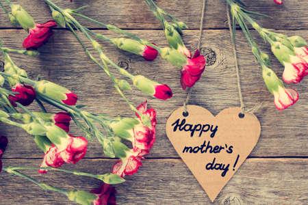 agradecimiento: Coraz�n Tarjeta del d�a de las madres en forma de claveles en el fondo de madera