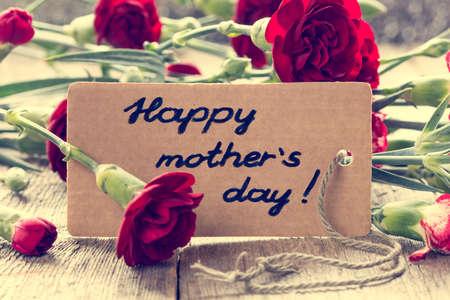 agradecimiento: Tarjeta del d�a de madres con claveles en la tabla de madera. filtro de la vendimia.