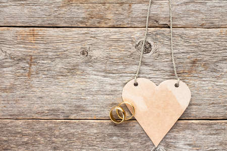 Gold wedding rings and paper heart nanging on wooden background Banco de Imagens