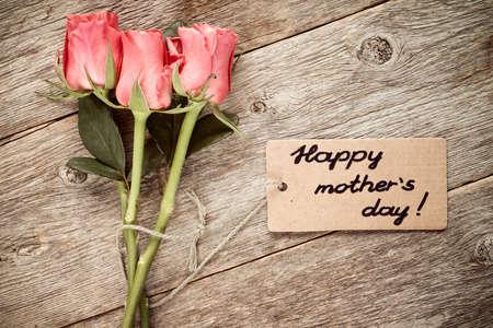 agradecimiento: Tarjeta del día de madres con rosas en la tabla de madera.