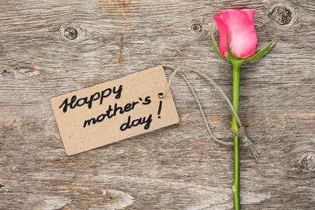gratefulness: Tarjeta del d�a de madres con rosa rosa sobre tabla de madera. Foto de archivo