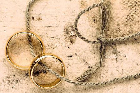 Twee gouden trouwringen gebonden met een touwtje