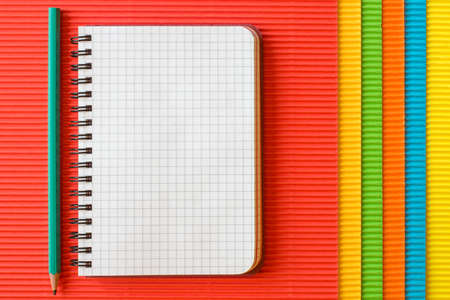 crimp: Blank  notebook with pencil on colored corrugated paper