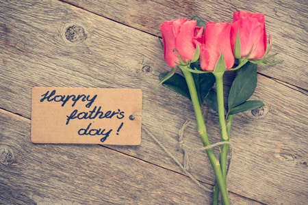 agradecimiento: Tarjeta del d�a de padre con rosas en la tabla de madera vieja.