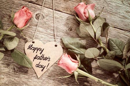 agradecimiento: Corazón en forma de tarjeta del día de padre con rosas rojas en el fondo de madera