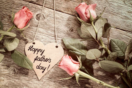 agradecimiento: Heart shaped fathers day card with red roses on wooden background Foto de archivo