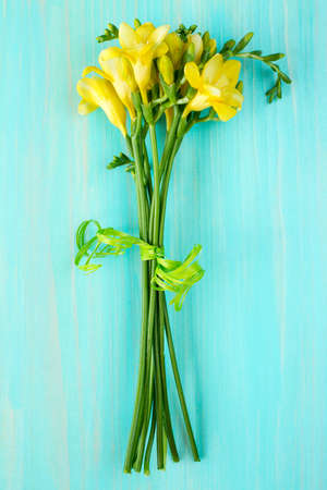 freesia: Bouquet of freesia flowers lying on the wooden background