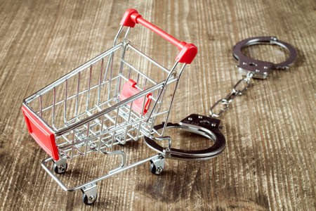 Shopping cart and handcuffs on old wooden background