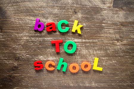 frase: Sentencia Volver a la escuela en letras de plástico de colores sobre fondo de madera oscura Foto de archivo