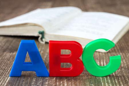 libro abierto: ortografía ABC y libro abierto sobre fondo de madera
