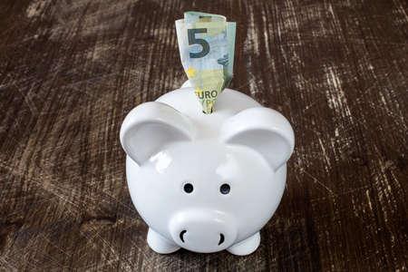 Detail van een spaarvarken en vijf euro biljet