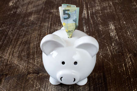 dinero euros: Detalle de una hucha y cinco billetes de euro