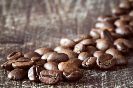 granule: Heap of coffee beans close-up on wooden background Stock Photo