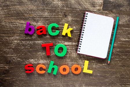 frase: Sentencia Volver a la escuela en letras de plástico de colores y un cuaderno en blanco sobre fondo de madera oscura