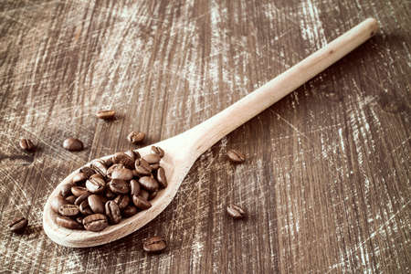 granule: Close-up of a wooden spoon filled with roasted cofee beans