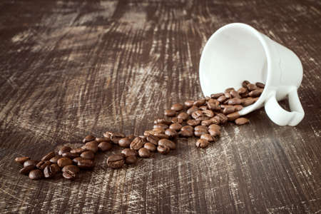 granule: Coffee-cup and roasted coffee beans on a wooden background.
