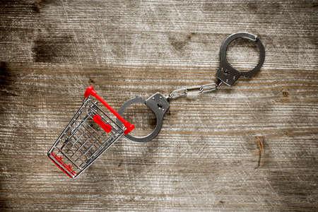 delincuencia: Carro de compras y esposas en vieja visi�n background.Top madera.
