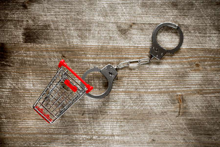 delinquency: Shopping cart and handcuffs on old wooden background.Top view.