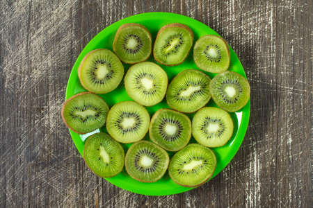 fruit plate: Fruit kiwi slices in a green plate, top view