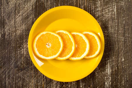 healthiness: Orange slices in a yellow plate, top view