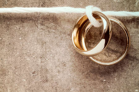 anillo de boda: Wedding rings hanging on rope over a dirty canvas background Foto de archivo