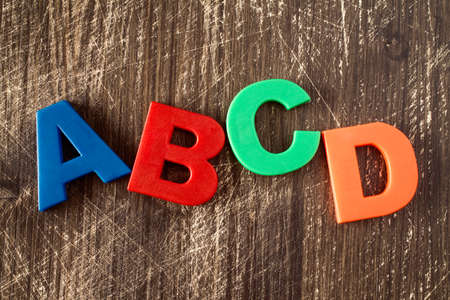 abcd: ABCD spelling from plastic letters on wooden background Stock Photo