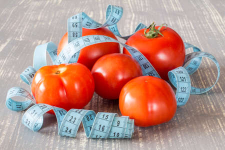 tailor measuring tape: Tomato fruits and tailor measuring tape on grey wooden background