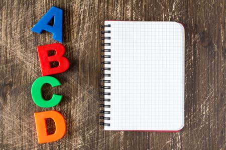 abcd: ABCD spelling from plastic letters and blank notebook on wooden background