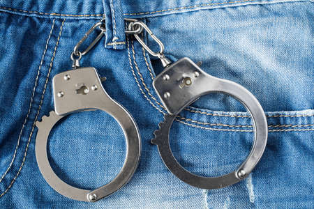 delincuencia: The handcuffs hanging on a belt of blue jeans Foto de archivo
