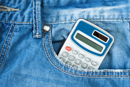 Digital electronic calculator in blue jeans pocket
