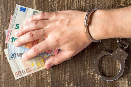 venality: Hand in handcuffs on Euro currency banknotes