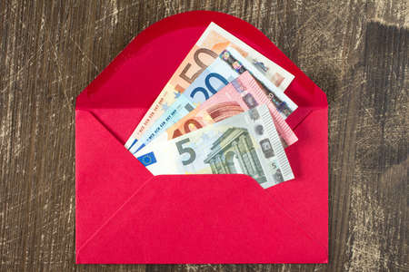 batch of euro: Red envelope with Euro bills over wooden background