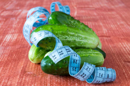 tailor measuring tape: Cucumber fruits and tailor measuring tape on grey wooden background Stock Photo