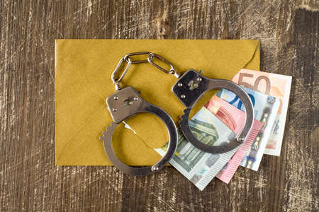 batch of euro: Envelope with Euro bills and handcuffs over wooden background