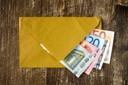 subornation: Golden envelope with Euro bills over wooden background Stock Photo