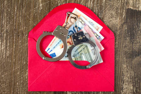 subornation: Red Envelope with Euro bills and handcuffs over wooden background