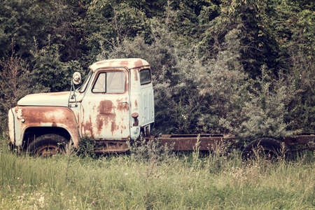 rusting: Abandoned old truck rusting in a field