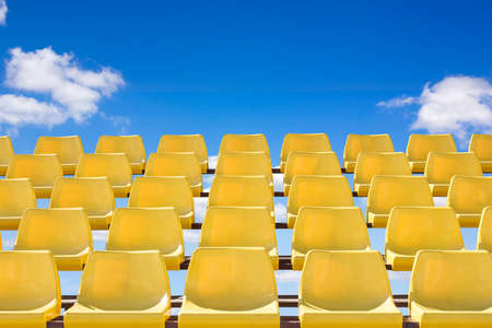 Yellow color sport stadium chair with blue sky background.Conceptual image.
