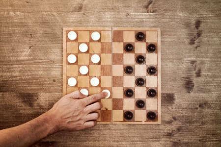 draughts: Man starting play draughts checkers board game Stock Photo