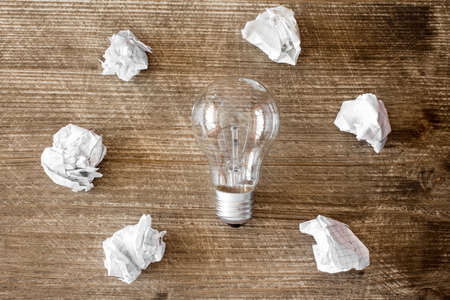Nuevo concepto de la idea con la bombilla y papel arrugado oficina