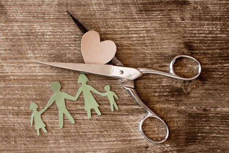 parental love: Scissors,cutout paper family and heart on wooden background