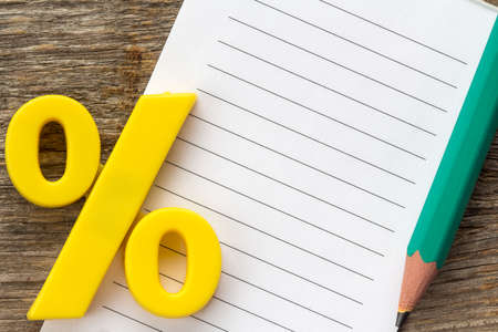 percentage sign: Note paper with pencil and yellow plastic percentage sign