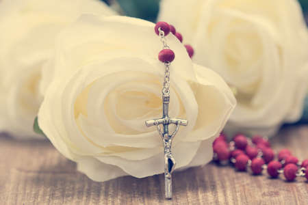 Catholic rosary and white roses on wooden background. Religion concept.