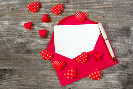 carta de amor: Love letter with red hearts on the wooden background Foto de archivo