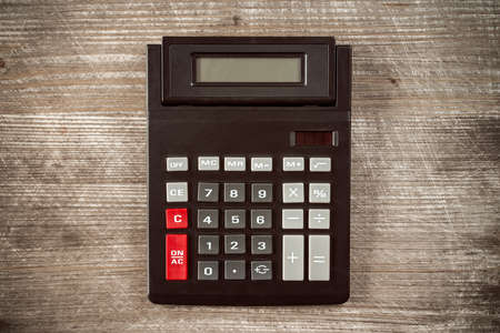computing machine: Top view of old calculator on wooden table Stock Photo